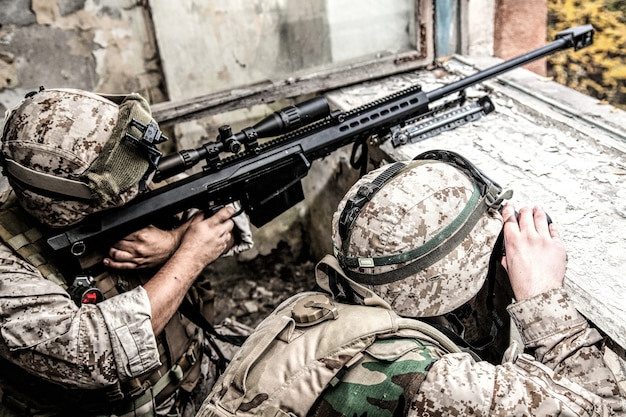 Marines sniper team armed with large caliber, anti-materiel sniper rifle hiding in ruined urban building, shooting enemy targets on range from shelter, sitting in ambush. military firefight in city