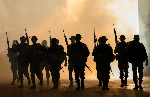 Marines team in action, surrounded fire and smoke, shooting with assault rifle and machine gun, attacking enemy