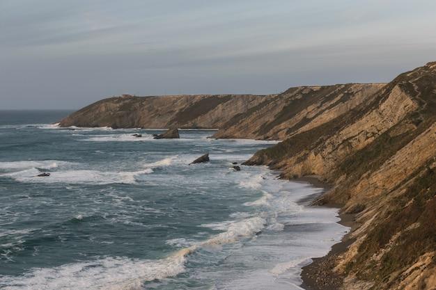 Морской фон. скалы и волнистое море.