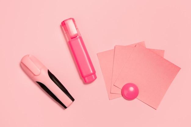 Маркер и бумажные наклейки. монохромный стильный и модный состав в розовом цвете на фоне студии. вид сверху, плоская планировка. чистая красота привычных вещей вокруг. copyspace для рекламы. офис.