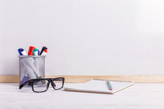 Markers, glasses, notebook, pencil and white board.