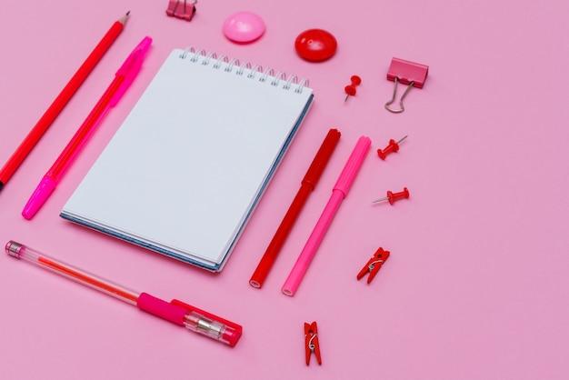 Маркеры разных розовых оттенков с белым блокнотом на розовом фоне ручки и карандаши вид сверху - это ...