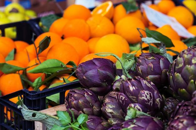 市場と果物。フォアグラウンドのアーティチョーク
