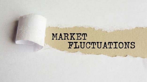 市場の変動。言葉。破れた紙の背景に灰色の紙のテキスト