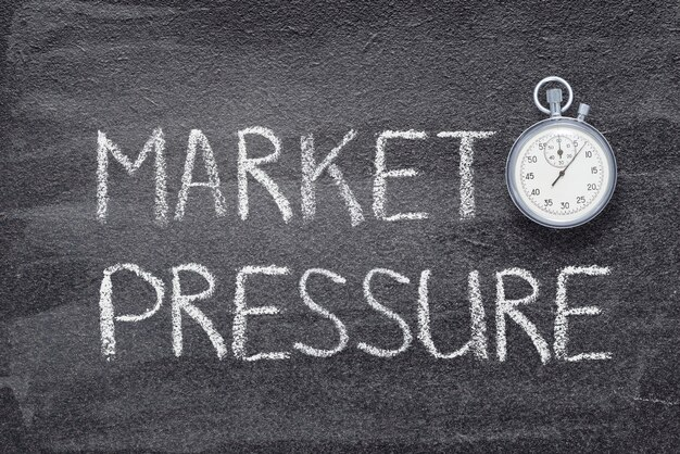 ヴィンテージの正確なストップウォッチで黒板に書かれた市場圧力フレーズ