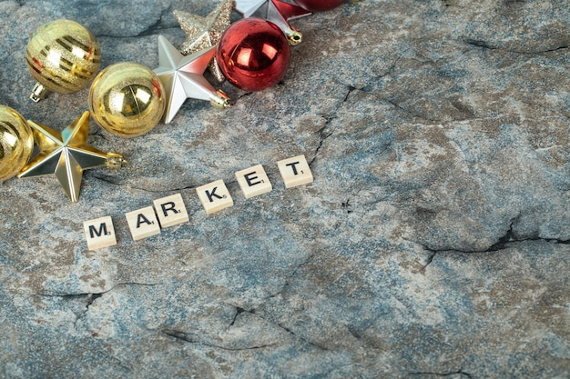 Market writing with black letters on wooden dices with christmas decorations around. high quality photo