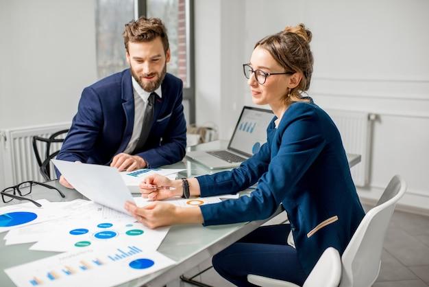 흰색 사무실 내부에서 종이 차트와 노트북으로 작업하는 정장을 입은 마케터 또는 애널릭 매니저 팀