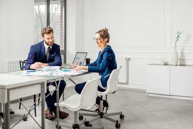 Команда маркетологов или аналитиков, одетых в костюмы, работающих с бумажными диаграммами и ноутбуками в интерьере белого офиса