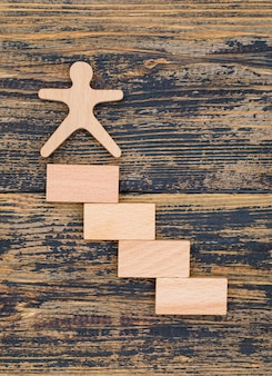 Marketing concept with wooden figure and blocks on wooden background flat lay.