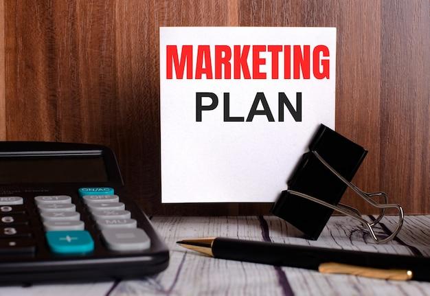 Маркетинговый план написан на белой карточке на деревянном фоне рядом с калькулятором и ручкой.