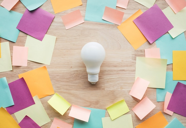 Marketing,planning ideas concepts with white lightbulb and colorful notepaper on wood table.nobody