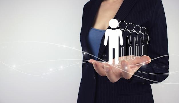 마케팅 세분화 및 리더 개념입니다. 회색 배경에 디지털 홀로그램 사람들을 손으로 잡으십시오. 최고 경영자