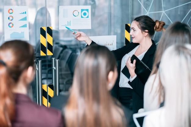 Семинар по маркетинговой стратегии. презентация спикера. молодая женщина, указывая на темпы роста.