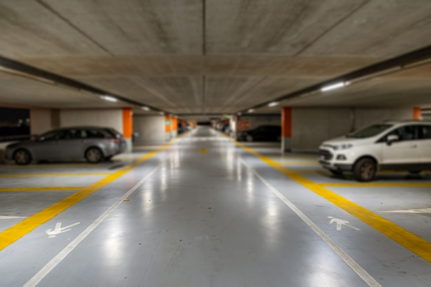Markings with blurred modern cars parked inside an underground parking lot.