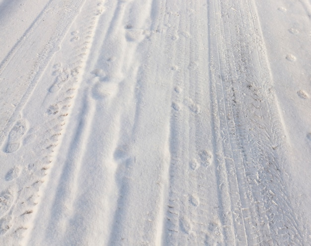 The marks of the vehicle wheels on snow-covered road. photographed close-up.