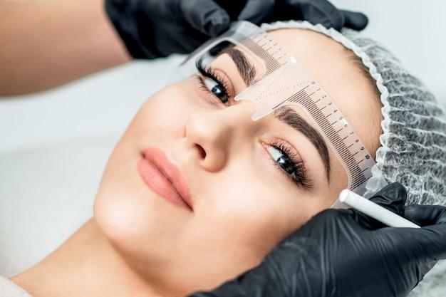 Разметка линейкой на бровях молодой женщины во время перманентного макияжа.