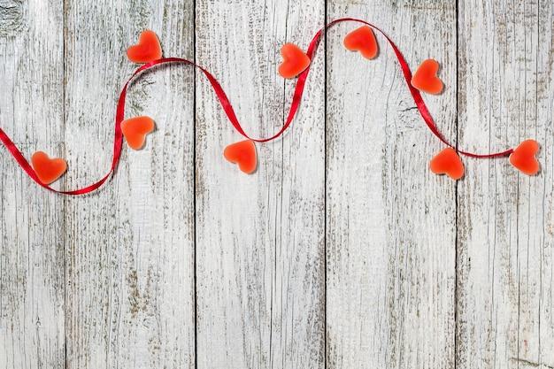 마멀레이드 사탕 모양 마음과 나무 테이블, 발렌타인 데이 구성, 인사말 카드에 빨간 리본.