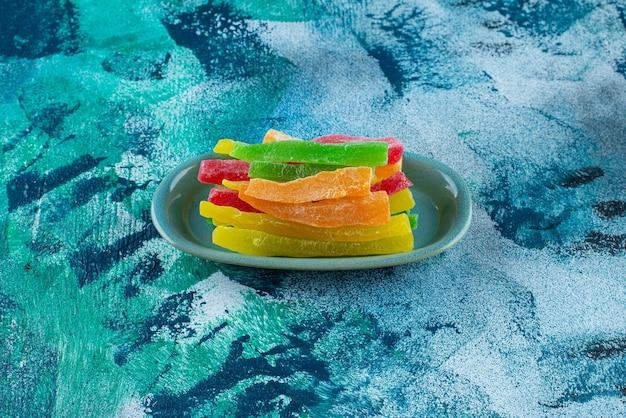 Marmellata sotto forma di bastoncini colorati in un piatto, sul tavolo blu.