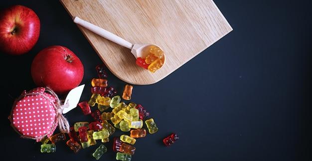 テーブルの上の花瓶のマーマレード。黒地にボウルに入ったお菓子。子供のための色とりどりのゼリーのお菓子。