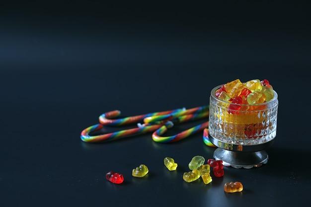 テーブルの上の花瓶のマーマレード。黒の背景にボウルにスイーツ。子供向けの色とりどりのゼリー菓子。