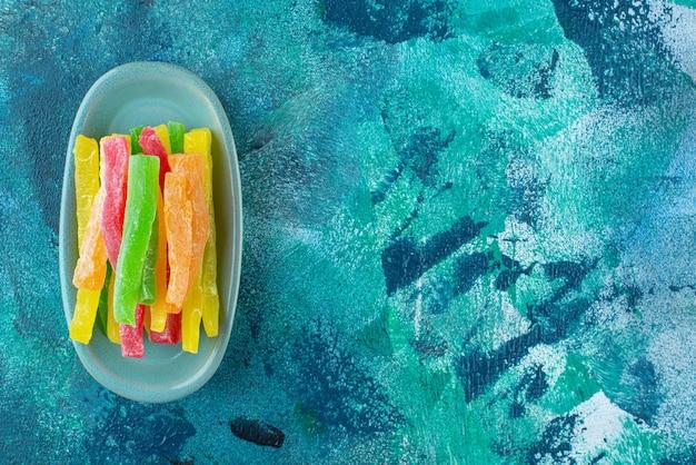 파란색 테이블에 접시에 색깔 막대기 형태의 마멀레이드.
