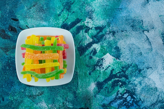 대리석 테이블에 접시에 색깔 막대기 형태의 마멀레이드.