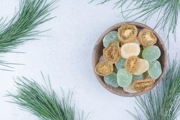 Мармелады и сушеные ломтики киви в деревянной миске.