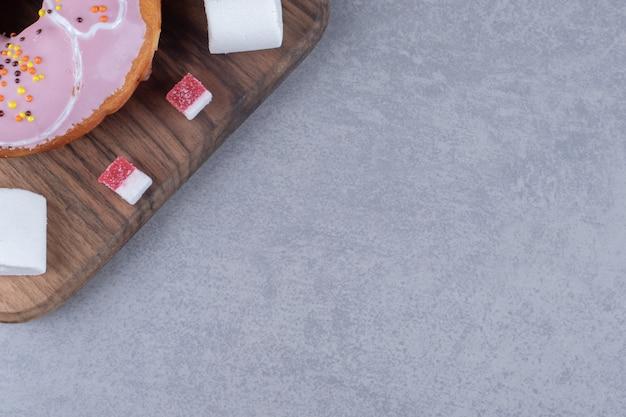 Мармеладные кусочки, зефир и пончик на деревянной доске на мраморной поверхности