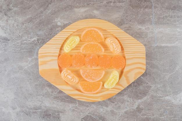 大理石の表面の木製の大皿にマーマレードの束