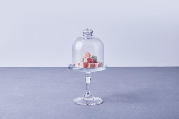 Конфеты мармелад в стеклянной чашке со стеклянной крышкой.