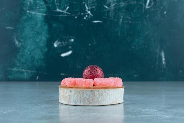 Anello di marmellata intorno a una pallina di natale su un pezzo di legno su blu.