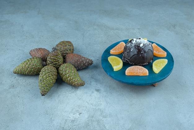 マーマレードと大理石の松ぼっくりの束の横にある小さな台座のケーキ。