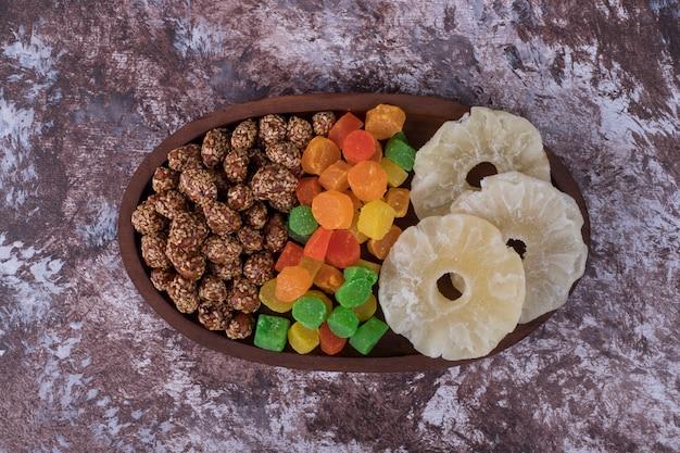 Мармелады и сухие нарезанные фрукты на деревянной тарелке посреди стола.