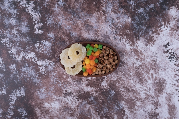 マーマレードとドライスライスフルーツ、大理石のテーブルに木製の大皿