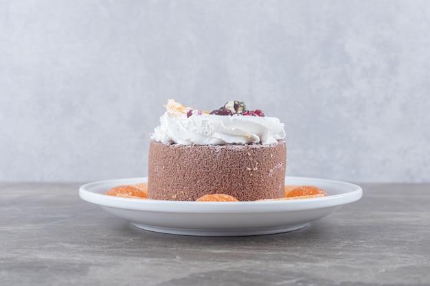 大理石の表面の大皿に小さなケーキの周りのマーマレード