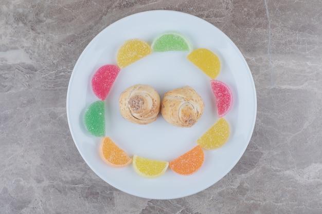 Marmellate intorno a minuscole torte su un vassoio su marmo