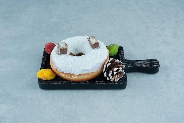 Marmelades, 솔방울 및 대리석에 검은 쟁반에 도넛.