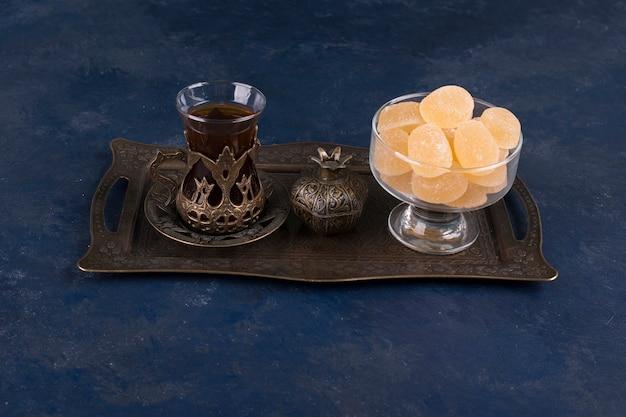 青い空間に分離された金属の大皿にお茶のグラスとマーマレード