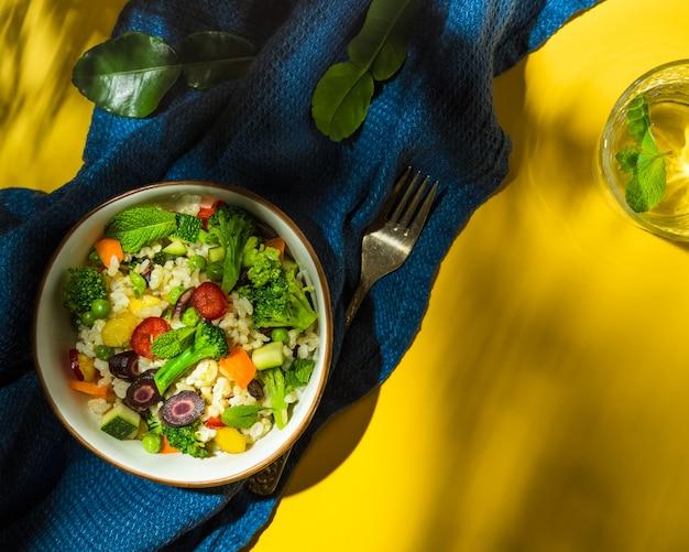 黄色と青の背景にモロッコ風ライスと野菜サラダ