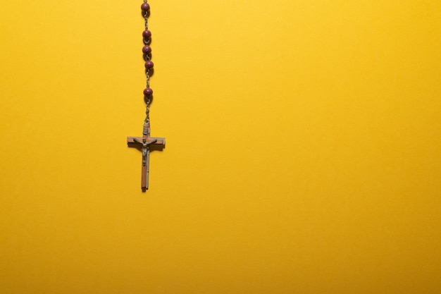 Maroon beads rosary with wooden crucifix on yellow