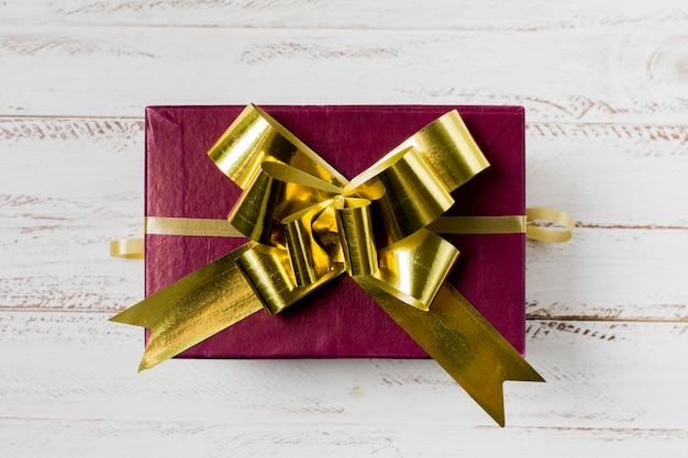 Maroon gift box with golden ribbon over wooden desk