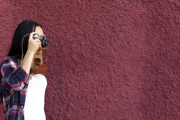 Портрет женщины фотографируя с камерой против maroon текстурированной стены