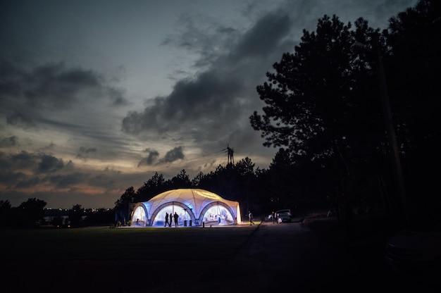 Шатер для празднования свадьбы. большой свадебный шатер на открытой площадке для приема гостей. вечернее фото с красивым закатом.
