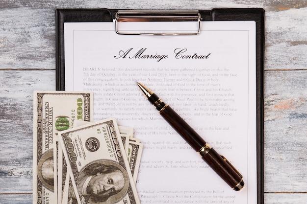 결혼 계약 펜과 돈. 모의 결혼 개념.