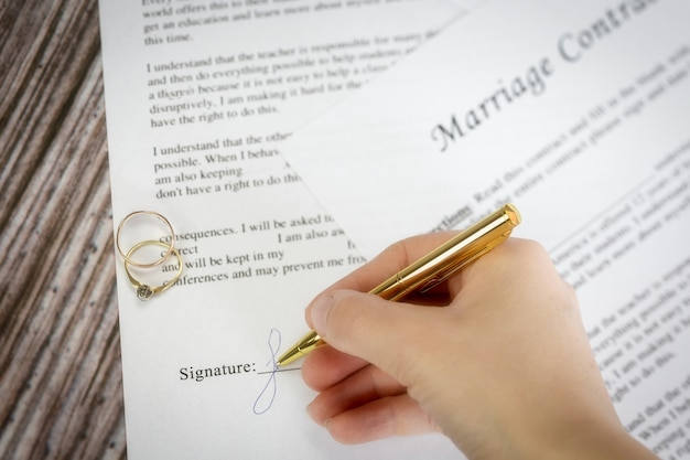 Marriage contract with two golden wedding rings and gold pen, prenuptial agreement, macro close up, sign with signanture,document,agreement concept romance