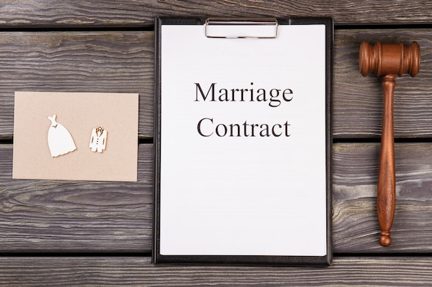 Marriage contract and wooden gavel on the desk.