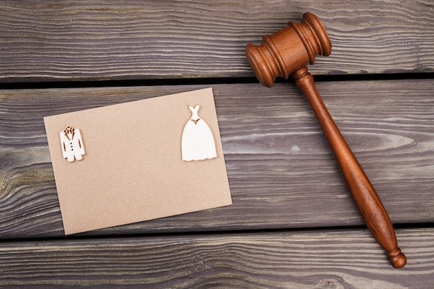 Marriage gavel and copy space on beige paper. brown wooden hammer on wood.