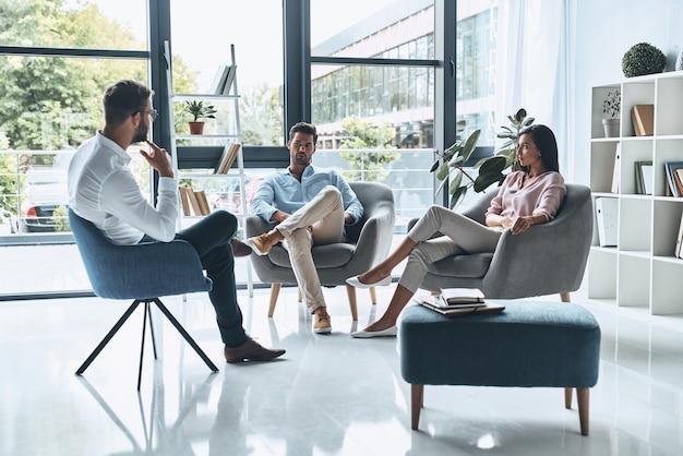 結婚の問題。心理学者との治療セッションに座って話している若い夫婦