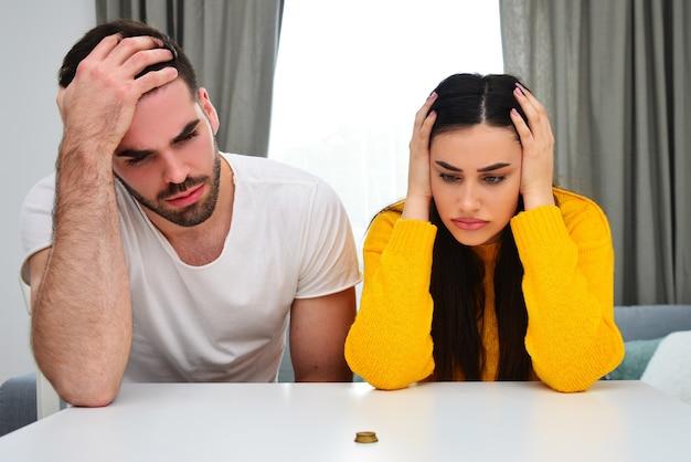 Проблемы в браке, денежные вопросы, ответственное обращение с деньгами, концепция сбережений. молодая пара, глядя на деньги на столе, беспокоит.