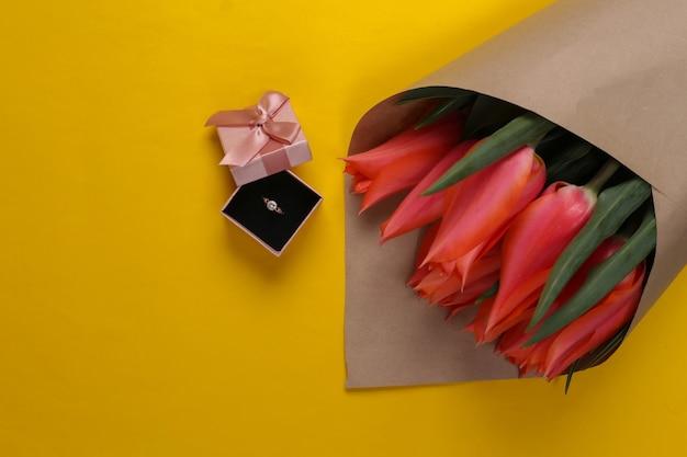 結婚の申し込み。チューリップの花束、黄色のギフト ボックスにダイヤモンドの付いたゴールデン リング